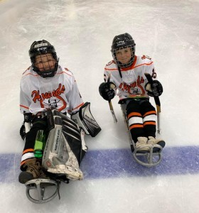 Two children playing sledge hockey